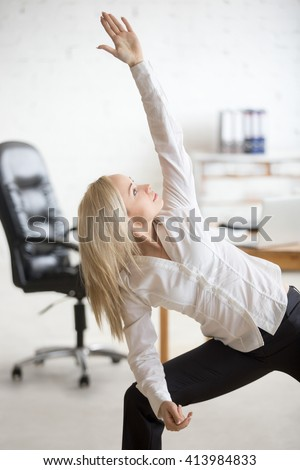 Business and healthy lifestyle concept. Portrait of young office woman standing in yoga pose at workplace. Happy beautiful business lady doing Extended Side Angle posture on her break time - stock photo