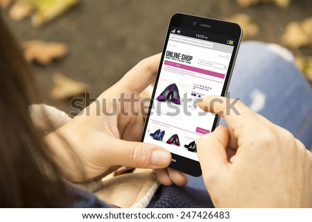 business and modern lifestyle concept: young woman shopping online at the park - stock photo