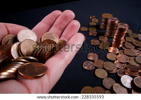 business and money saving concept - close up of female hand with euro cents and column of money - stock photo