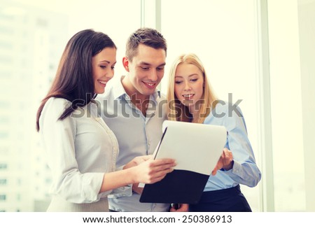 business and office concept - business team looking at clipboard - stock photo