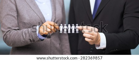 business and office concept - businessman and businesswoman holding paper team in office - stock photo