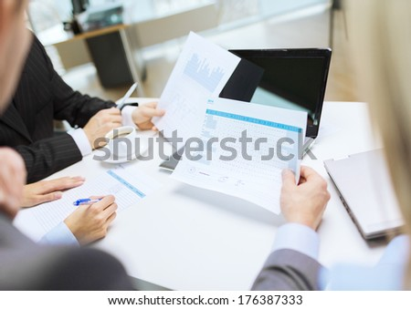 business and office concept - close up of business team with files and laptop computer in office - stock photo