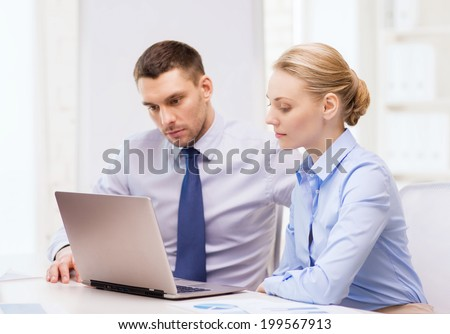 business and office concept - serious business team working with laptop computer in office - stock photo