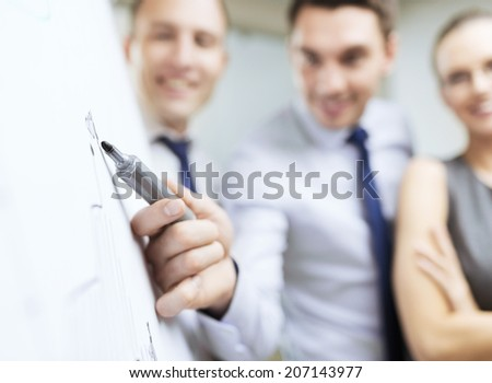 business and office concept - smiling business team with charts on flip board having discussion - stock photo