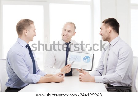 business and office concept - smiling businessman showing others charts in office - stock photo