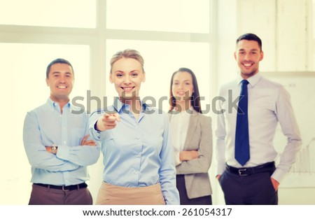 business and office concept - smiling handsome businesswoman with team in office pointing finger at you - stock photo