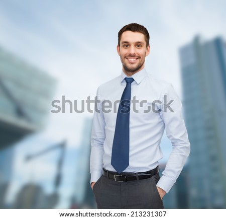 business and people concept - smiling young and handsome businessman over business centre background - stock photo