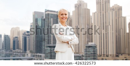 business and people concept - young smiling businesswoman with crossed arms over dubai city background - stock photo