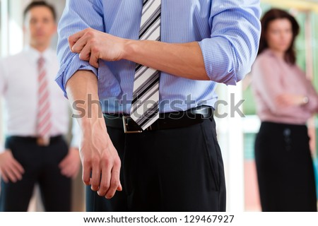 Business and people - roll up the sleeves as a business metaphor, close-up - stock photo