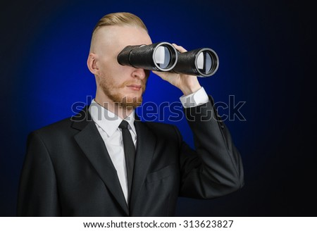 Business and search topic: Man in black suit holding a black binoculars in hand on a dark blue background in studio isolated - stock photo