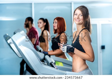 Business and sports. Sport and slender girl running on a treadmill and holding a mobile phone. Athlete dressed in sports uniforms and running in the gym and looking at the camera. - stock photo