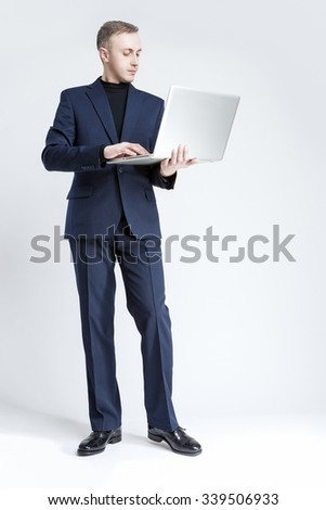 Business and Technology Concept. Portrait of Young and Smiling Handsome Caucasian Businessman in Blue Suit Standing With Laptop Computer for Communication. Against Gray. Vertical Image Orientation - stock photo