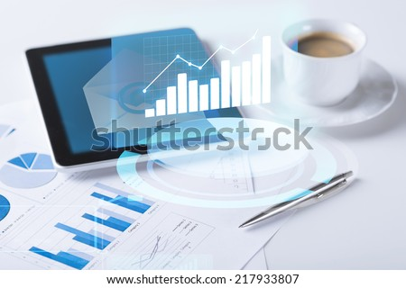 business and technology concept - tablet pc and cup of coffee with chart projection - stock photo