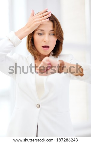 business and time management concept - stressed businesswoman looking at wrist watch in office - stock photo