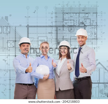 business, architecture and office concept - happy team of architects in office showing thumbs up - stock photo