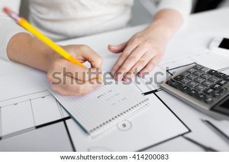business, architecture, building, construction and people concept - close up of architect hand with blueprint and calculator writing to notebook - stock photo