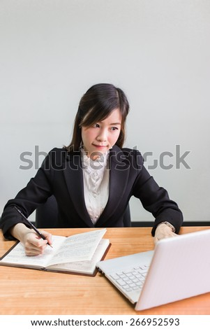 Business asian woman Writing on a Paper While searshing data on her Laptop Computer - stock photo