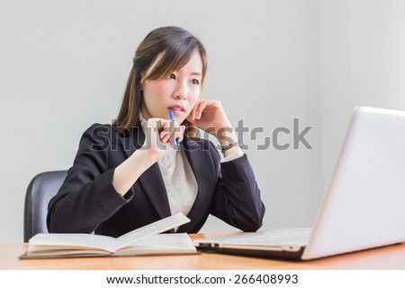 Business asian woman Writing on a Paper While searshing data on her Laptop Seriously. - stock photo