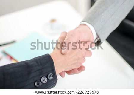 Business associates shaking hands at office, closeup - stock photo