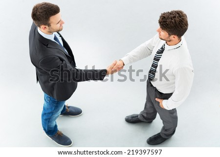 Business associates shaking hands, high angle view - stock photo