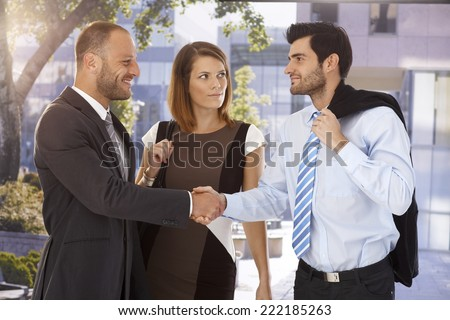 Business associates shaking hands on the street in front of bank center building. - stock photo