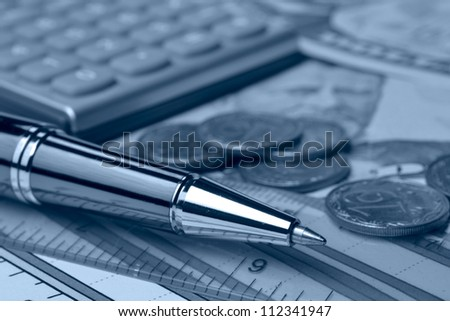 Business background in blues with table, coins and pen. - stock photo