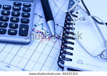 Business background with charts, pen and calculator in blue hue - stock photo