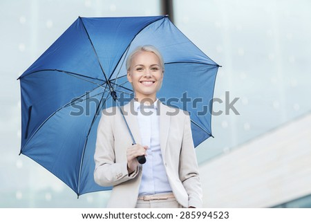 business, bad weather and people and concept - young smiling businesswoman with umbrella outdoors - stock photo