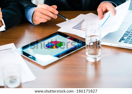 Business - banker, Manager or expert evaluates the figures on tablet computer and compares the development of the business in real time - stock photo
