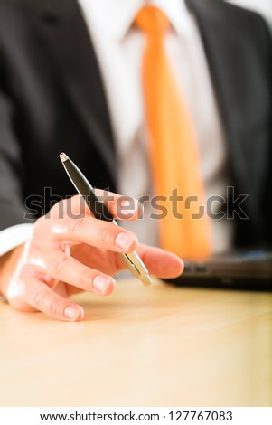 Business - Boss in his office checking mails, in his hand he holds a pen, closeup - stock photo