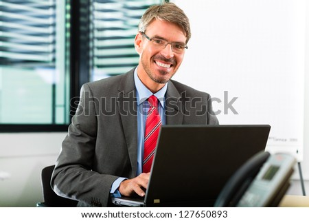 Business - Boss in his office checking mails on laptop computer - stock photo