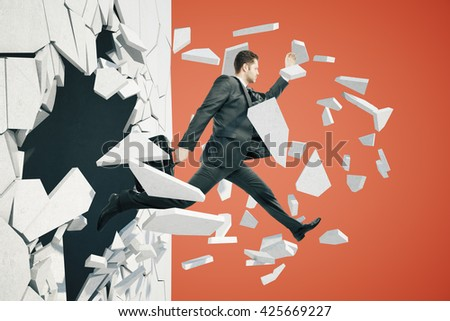 Business breakthrough success concept with businessman jumping through wall on red background - stock photo