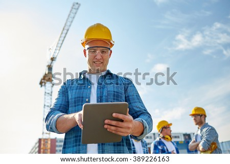business, building, industry, technology and people concept - smiling builder in hardhat with tablet pc computer over group of builders at construction site - stock photo