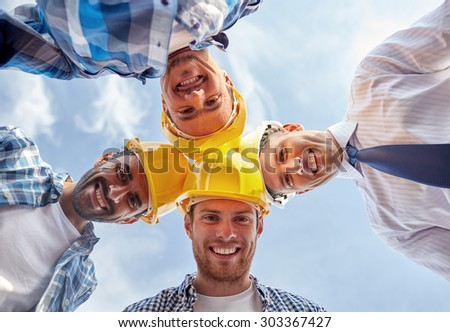 business, building, partnership, construction and people concept - close up of smiling builders and architect in hardhats in circle outdoors - stock photo