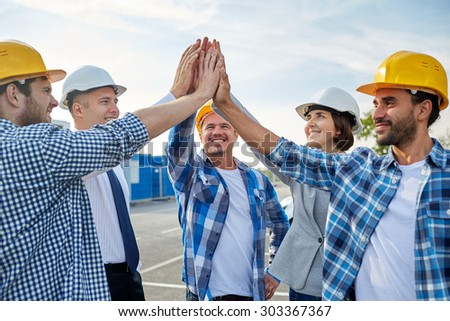 business, building, partnership, gesture and people concept - close up of smiling builders and architects in hardhats making high five outdoors - stock photo