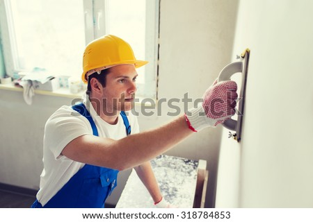 business, building, profession and people concept - builder with grinding tool indoors - stock photo