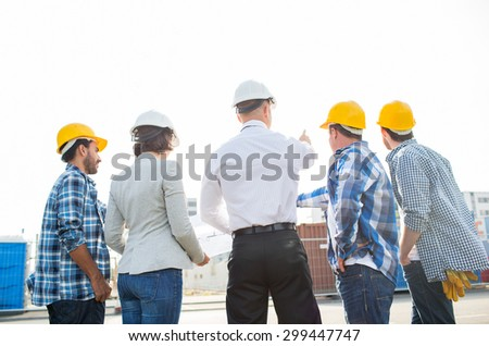 business, building, teamwork and people concept - group of builders and architects in hardhats with blueprint on construction site - stock photo