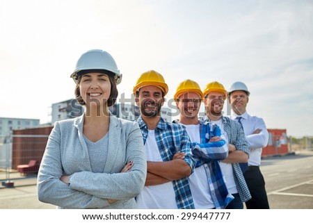 business, building, teamwork and people concept - group of smiling builders and architect in hardhats at construction site - stock photo