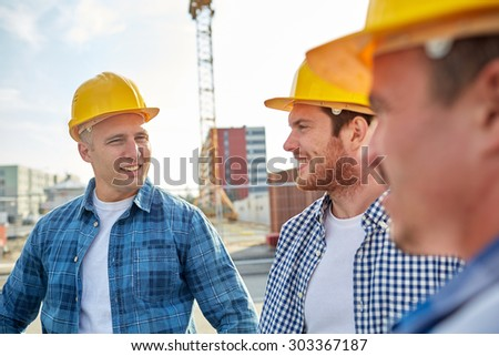 business, building, teamwork and people concept - group of smiling builders in hardhats at construction site - stock photo