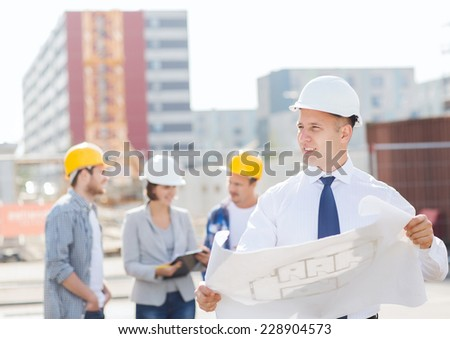 business, building, teamwork and people concept - group of smiling builders in hardhats with clipboard and blueprint outdoors - stock photo