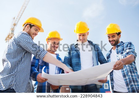 business, building, teamwork and people concept - group of smiling builders in hardhats with blueprint outdoors - stock photo