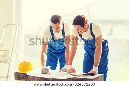 business, building, teamwork and people concept - group of smiling builders with blueprint and hardhat indoors - stock photo