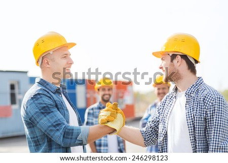 business, building, teamwork, gesture and people concept - group of smiling builders in hardhats greeting each other with handshake outdoors - stock photo