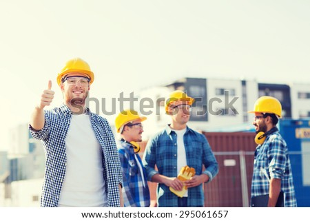 business, building, teamwork, gesture and people concept - group of smiling builders in hardhats showing thumbs up outdoors - stock photo