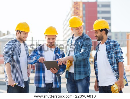 business, building, teamwork, technology and people concept - group of smiling builders in hardhats with tablet pc computer and clipboard outdoors - stock photo