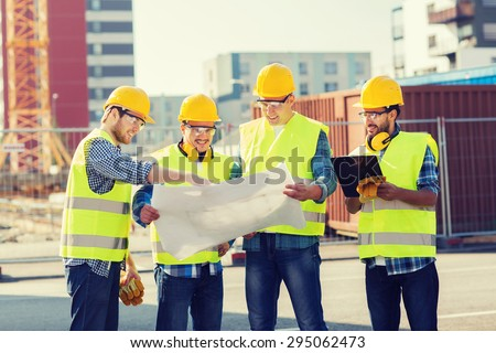 business, building, teamwork, technology and people concept - group of smiling builders in hardhats with tablet pc computer and blueprint outdoors - stock photo