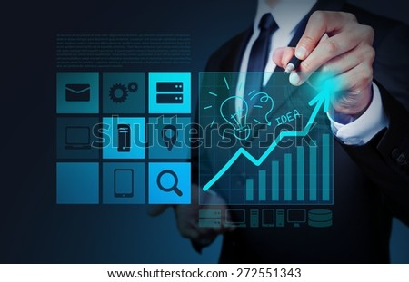 Business. Businessman hand draws lightbulb with new computer interface as solution business concept - stock photo