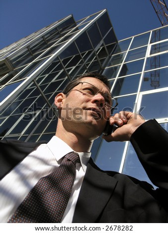 Business call. Young businessman talking to the cell phone in front of an office  . - stock photo