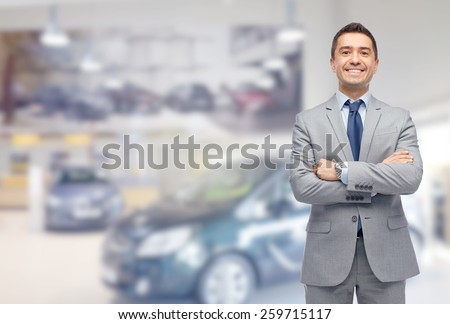 business, car sale, consumerism and people concept - happy man over auto show or salon background - stock photo