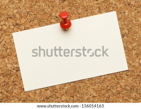 Business card posted on a cork board with red tack pin. - stock photo